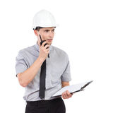 Engineer with clipboard using walkie talkie. Royalty Free Stock Image