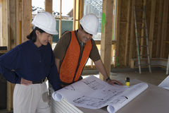 Engineer And Co-Worker Working Over Blueprint Stock Images