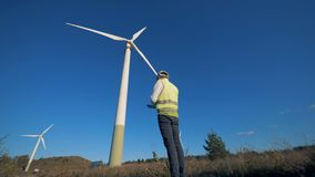 An engineer comes closer to tower turbines and is making calculations