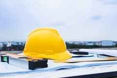 Engineer constrction safety helmet and other tools on top of building blueprint outside at construction site royalty free stock images