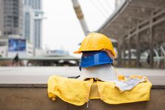 Engineer construction equipment in city. Engineering construction equipment of Safety helmet hats, gloves, and yellow worker dress on concrete floor with blurred royalty free stock images