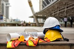 Engineer and construction equipment in city. Safety helmet hats, blueprint paper project, measure tape, gloves, and worker dress on concrete floor at modern city Stock Photos