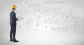 Engineer holding a plan and standing with graphs, charts and reports on the background royalty free stock images