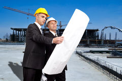 Engineer at a construction site. Engineer looking at a plan at a construction site Royalty Free Stock Photos
