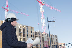 An engineer on a construction site with cranes and blueprints in hands Stock Photography