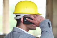 Engineer at a construction site making a business call. Photo of the Engineer at a construction site making a business call Royalty Free Stock Photo