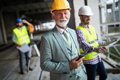 Engineer and construction site manager dealing with blueprints and plans royalty free stock photo