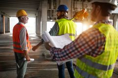 Engineer and construction site manager dealing with blueprints and plans royalty free stock image