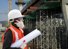 Engineer a construction site using cellphone. Engineer On A Construction Site Using A Mobile Cellphone Stock Image
