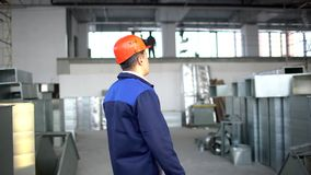 Engineer, Construction supervisor, builder, worket using laptop at a construction site inside. airduct of an HVAC system. Engineer Construction supervisor stock video footage