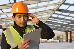 Engineer construction talking mobile phone under new building. Engineer construction with savety vest  talking mobile phone under new building Stock Photos