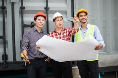 Engineer and construction team wearing safety helmet and blueprint on hand. they are checking progress of construction site. Engineer and construction team royalty free stock photo