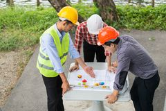 Engineer and construction team wearing safety helmet and looking blueprint on the table. They are working on checking progress of construction site. engineer stock image