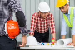 Engineer and construction team wearing safety helmet and working by checking progress of construction in blueprint. Engineer and construction team wearing Royalty Free Stock Photo