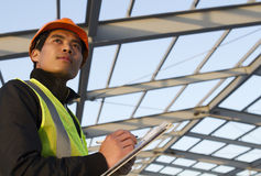 Engineer construction under new building checking plan. Horizontal image royalty free stock photography