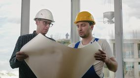 Engineer and construction worker discuss a blueprint. Medium shot.Engineer and construction worker discuss a blueprint. Professional shot in 4K resolution. 025 stock footage