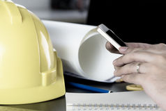 Engineer construction worker is using phone in office cable. Stock Photography
