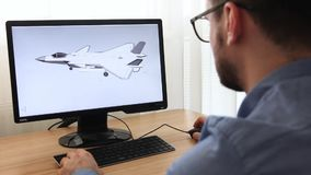 Engineer, constructor, designer in glasses working on a personal computer. He is creating, designing a new 3 d model of aircraft,. Airplane in cad program stock video footage