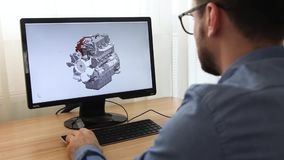Engineer, constructor, designer in glasses working on a personal computer. He is creating, designing a new 3 d model of car engine. Engineer, constructor stock video