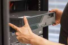 IT Consultant Install Network Router. It engineer / consultant install / inserts a router / switch in a rack. Shot in a data center Stock Photography