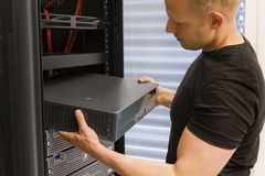 IT Consultant Install Network Router. It engineer / consultant install / inserts a router / switch in a rack. Shot in a data center Stock Photos