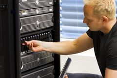 IT Consultant Maintain SAN and Servers. It engineer / consultant working in a data center. This enclosure is a SAN (storage area network) and servers at the top Royalty Free Stock Image