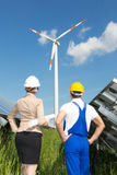 Engineer and contractor posing in front of wind turbine Stock Images