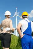Engineer and contractor posing in front of wind turbine Royalty Free Stock Photos