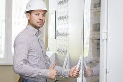 Engineer in control panel room. Worker in white helmet on industrial tech station. Engineer on a job. Engineer in control panel room. Worker in white helmet on Royalty Free Stock Image