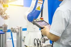 The engineer control the robotic arm for manufacturing process. stock photo