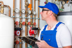 Engineer controlling the heating system. Engineer controlling the heating pipes at the boiler room Stock Photography