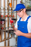 Engineer controlling the heating system. Engineer controlling the heating pipes at the boiler room Stock Images