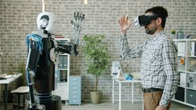 Engineer controlling robot using virtual reality glasses, machine copying gestures