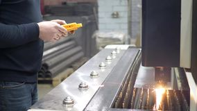 Engineer controls metal cutting process on CNC Laser machine. With a yellow remote control stock footage
