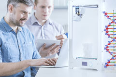 Engineer with 3d printer. Handsome engineer with new 3d printer and laptop Royalty Free Stock Images