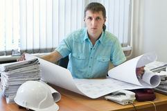 Engineer with design drawings in office. Engineer young adult male with project drawings in office. Working place. One man stock image