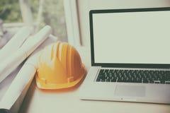 Engineer desk with laptop computer, orange helmet, blueprint rol Royalty Free Stock Images