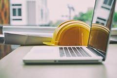 Engineer desk with laptop computer, orange helmet, blueprint rol Stock Images