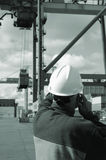 Engineer directing crane. Engineer with mobile telephone directing crane and container in mid-air, busy commercial port, all in a greenish toning concept Royalty Free Stock Photo
