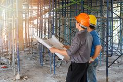Engineer discussing with foreman about project in building construction site stock photography