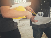 Engineer discussing with foreman about project. In building construction site royalty free stock images