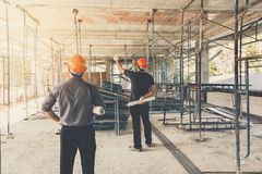 Engineer discussing with foreman about project in const. Engineer discussing with foreman about project in building construction site royalty free stock image