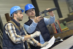 Engineer discussing with mechanical worker on products Stock Photos