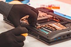 Engineer dismantles the details of a broken laptop for repair. Engineer dismantles the details of a broken laptop for repair royalty free stock image