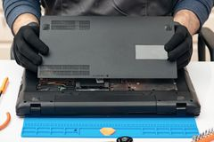 Engineer dismantles the details of a broken laptop for repair. Engineer dismantles the details of a broken laptop for repair stock photography