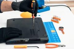 Engineer dismantles the details of a broken laptop for repair. Engineer dismantles the details of a broken laptop for repair stock photo