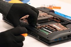 Engineer dismantles the details of a broken laptop for repair. Engineer dismantles the details of a broken laptop for repair royalty free stock images