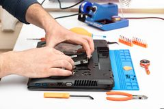 Engineer dismantles the details of a broken laptop for repair. Engineer dismantles the details of a broken laptop for repair stock photos