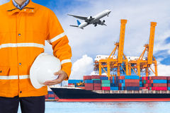 Engineer dockers wearing safety coat and holding a helmet. In front of an industrial harbor with cranes and a container ship being unloaded for logistic Import Royalty Free Stock Images