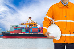 Engineer dockers wearing safety coat and holding a helmet. In front of an industrial harbor with cranes and a container ship being unloaded for logistic Import Stock Photo